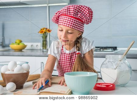 little girl baker reading a recipe on kitchen