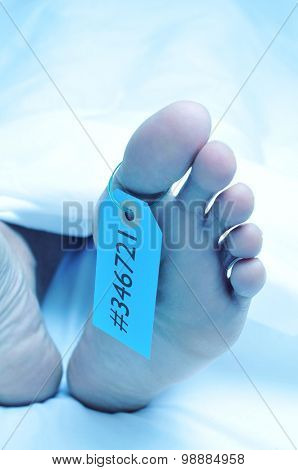 closeup of the feet of a dead body covered with a sheet and with a tag with an identification number tied on the big toe