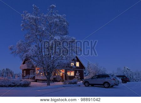 Winter house and vehicles in the night.