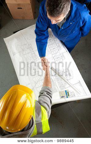 Two Builders Shake Hands Over Blueprint