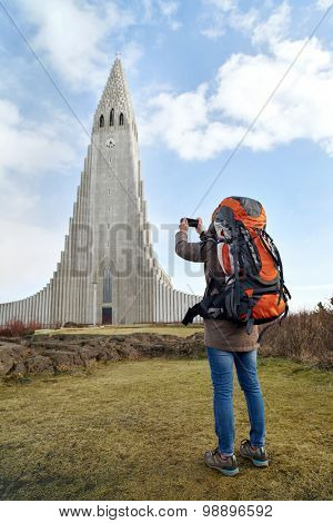 rear view of backpacker tourist travel woman taking pictures of the Hallgrimskirkja cathedral in reykjavik iceland