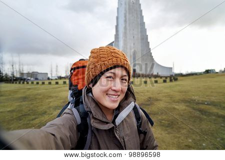 happy Asian Chinese woman taking travel tourist selfie with the Hallgrimskirkja cathedral in reykjavik iceland in the background