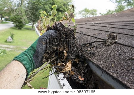 Worker cleaning gutters on a house for a customer. poster