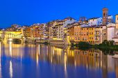 Old houses and tower on the embankment of the River Arno and Ponte Vecchio at night, Florence, Tuscany, Italy poster