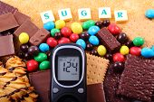 Glucose meter with word sugar heap of candies cookies and brown cane sugar too many sweets unhealthy food concept of diabetes and reduction of eating sweets poster