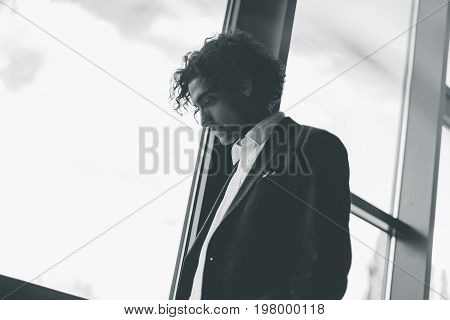 Black And White Portrait Of Thoughtful Businessman At Window Looking Away