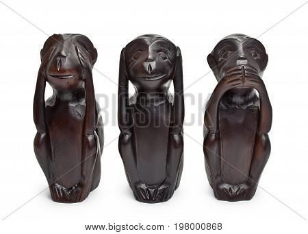 Three wooden figures of monkeys on a white background. See nothing, hear nothing, say nothing