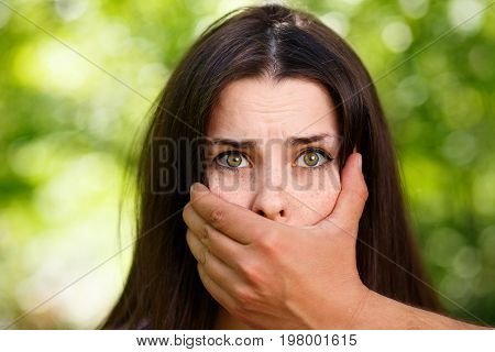 Closeup Image Of A Man's Hand Covering A Scared Woman's Mouth