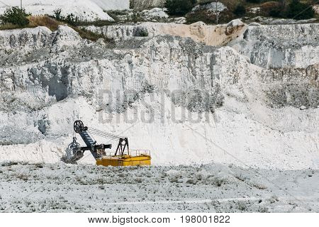 Yellow excavator works in a white chalk quarry. Industrial extraction or mining of minerals.
