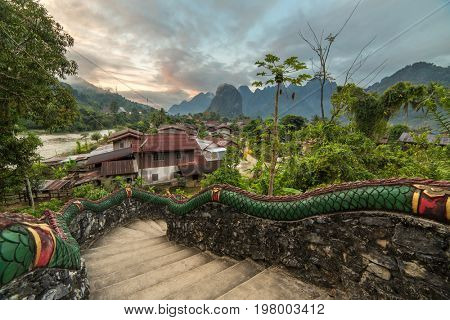 Traditional lao village with temple stairs and mountain background near Vang Vieng, Laos.