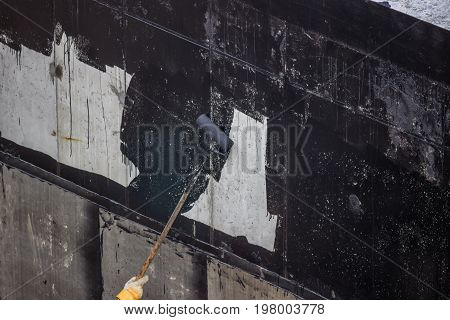 Waterproofing, Worker Painting Exterior Concrete Wall With Tar Insulation Material