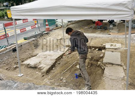 Lucerne Switzerland - June 14 2017: Archeology excavation site with man conducting scientific research in the ground in the centre of old city