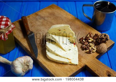Slices Of Spicy Cheese, Served With Walnuts,garlic And Mug Of Ho