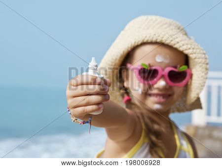 Happy child in glasses with sunscreen on a sea background. The focus of the tube.