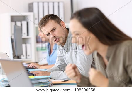 Jealous Employee Looking At A Successful Colleague