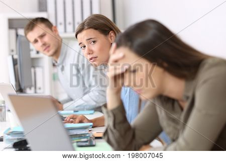 Sad workers looking at a frustrated colleague who is reading bad news on line at office poster