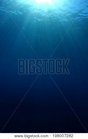 Underwater nature background of sunbeams in blue ocean water