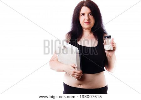 Young Overweight Woman With Scale And Pills In Hands