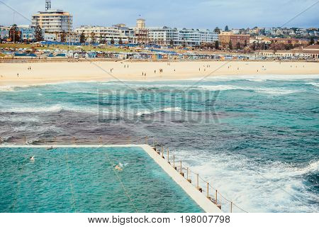 Sydney Australia - November 8 2015: Bondi Beach skyline view with people having fun viewed across swimming pool on a day