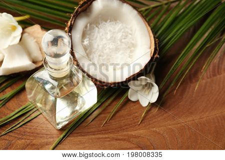 Platter with bottle of oil, coconut and palm leaf, closeup