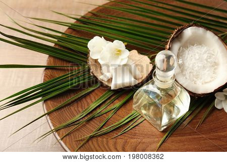 Platter with bottle of oil, coconut and palm leaf on wooden table