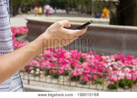 Hand of an anonymous man talking phone in park