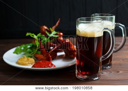 Two Mugs Of Dark Beer With Delicious Hot Crusty Grilled Chicken