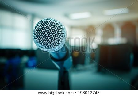 Microphone on abstract blurred of speech in seminar room or speaking conference hall light computer bokeh background