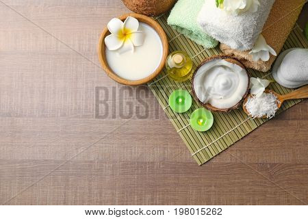 Beautiful spa composition with coconut body care products on bamboo mat