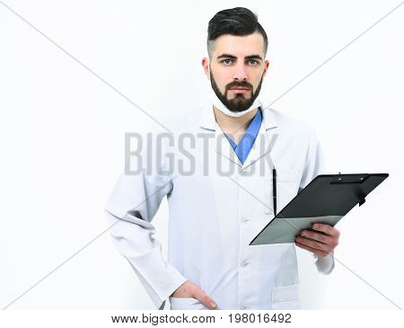 Doctor with beard holds clip folder for prescriptions. Dentist in surgical mask isolated on white background. Man with confident face in white medical coat. Treatment and ambulance services concept