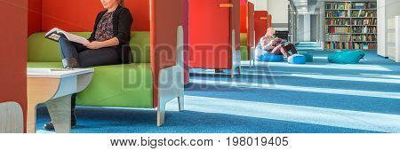 Banner view of library with individual study area with red partition and green sofa