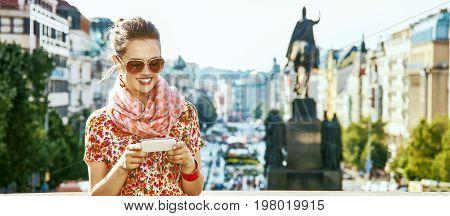The spirit of old Europe in Prague. happy modern traveller woman on Vaclavske namesti in Prague Czech Republic writing sms poster