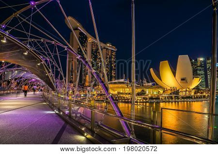 SINGAPORE - JUNE 17 2014 : Bridge to Marina Bay Sands Hotel in evening in Singapore