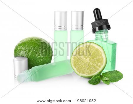 Bottles with perfume, leaves of mint and lime on white background