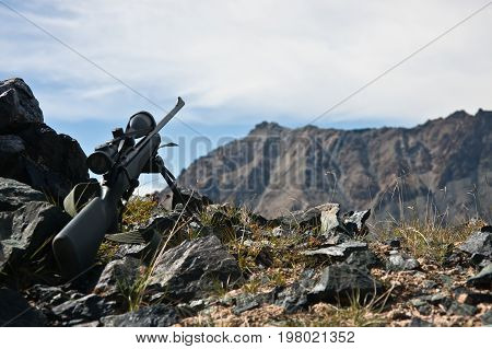 A hunting rifle with a telescopic sight a bipod while hunting in the Mountains of Tien Shan Kyrgyzstan