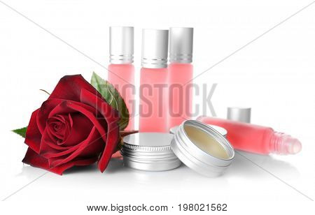Bottles, containers with perfume and rose on white background