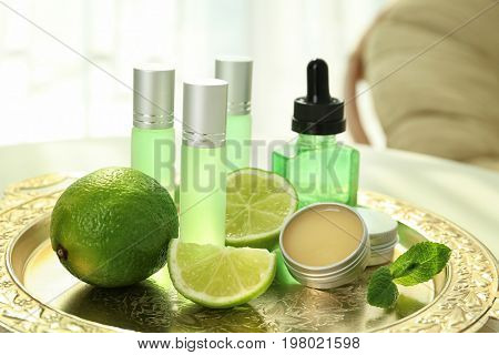 Tray with perfumes, limes and mint leaves on light background