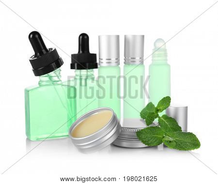 Bottles, containers with perfume and leaves of mint on white background