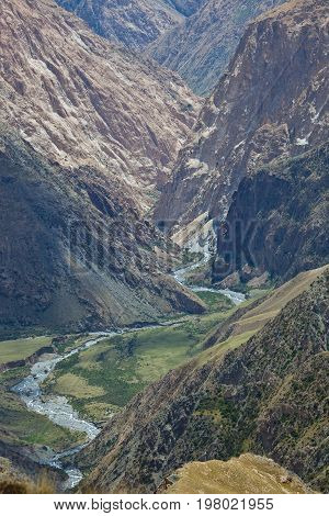 Rocky deep gorge and the mountain river in Tien Shan Kyrgyzstan. Steep slopes precipices cliffs and scree in the mountains inaccessible
