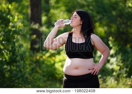 Young Thirsty Overweight Woman Drinking Water After Jogging In T