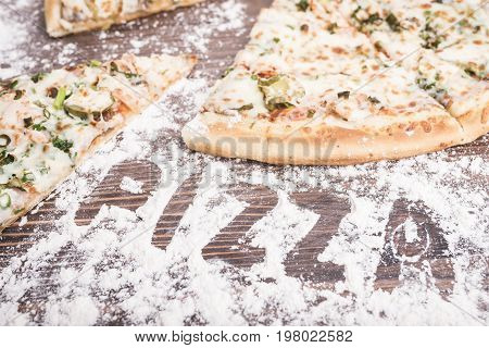 Pizza on a brown wooden background sprinkled with flour