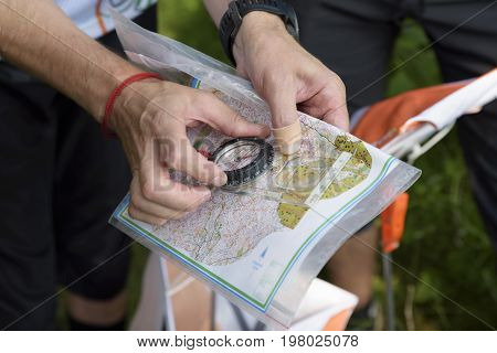 Compass and map for orienteering. Man reading map