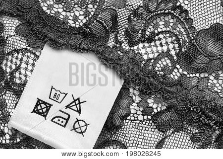 Washing instructions clothes label on black lace closeup