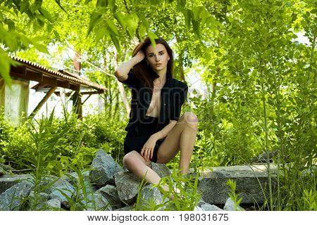 beautiful sensual girl in black suit seated on rocks in nature