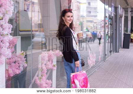 sweet charming lady near urban shops worth with packages and smiles