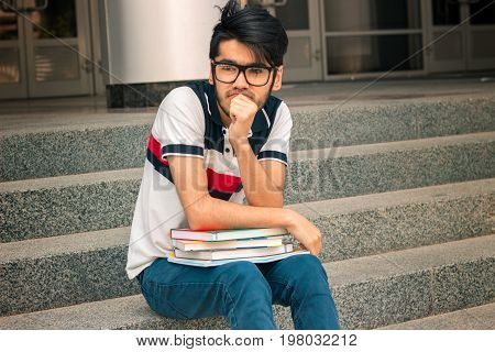 young charming guy in glasses to read sitting thinking with books in his hands