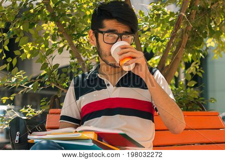 beautiful glamorous guy drinks coffee and keeps a book in hand, close-up