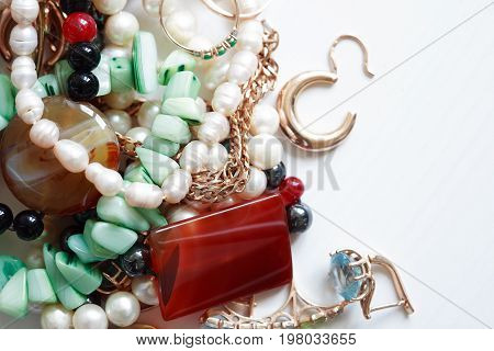 Set of various jewelry adornments on white wooden background with free space