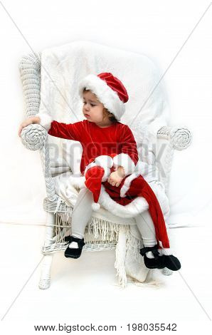 Little girl dressed in a santa claus costume sits and waits on Santa. She is sitting ina white chair in a white room.