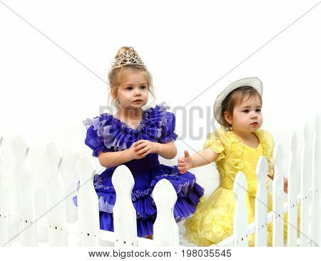 Two adorable little girls stand behind a white picket fence. They are wearing pageant dresses in yellow and purple. One has on a tiara the other a hat.